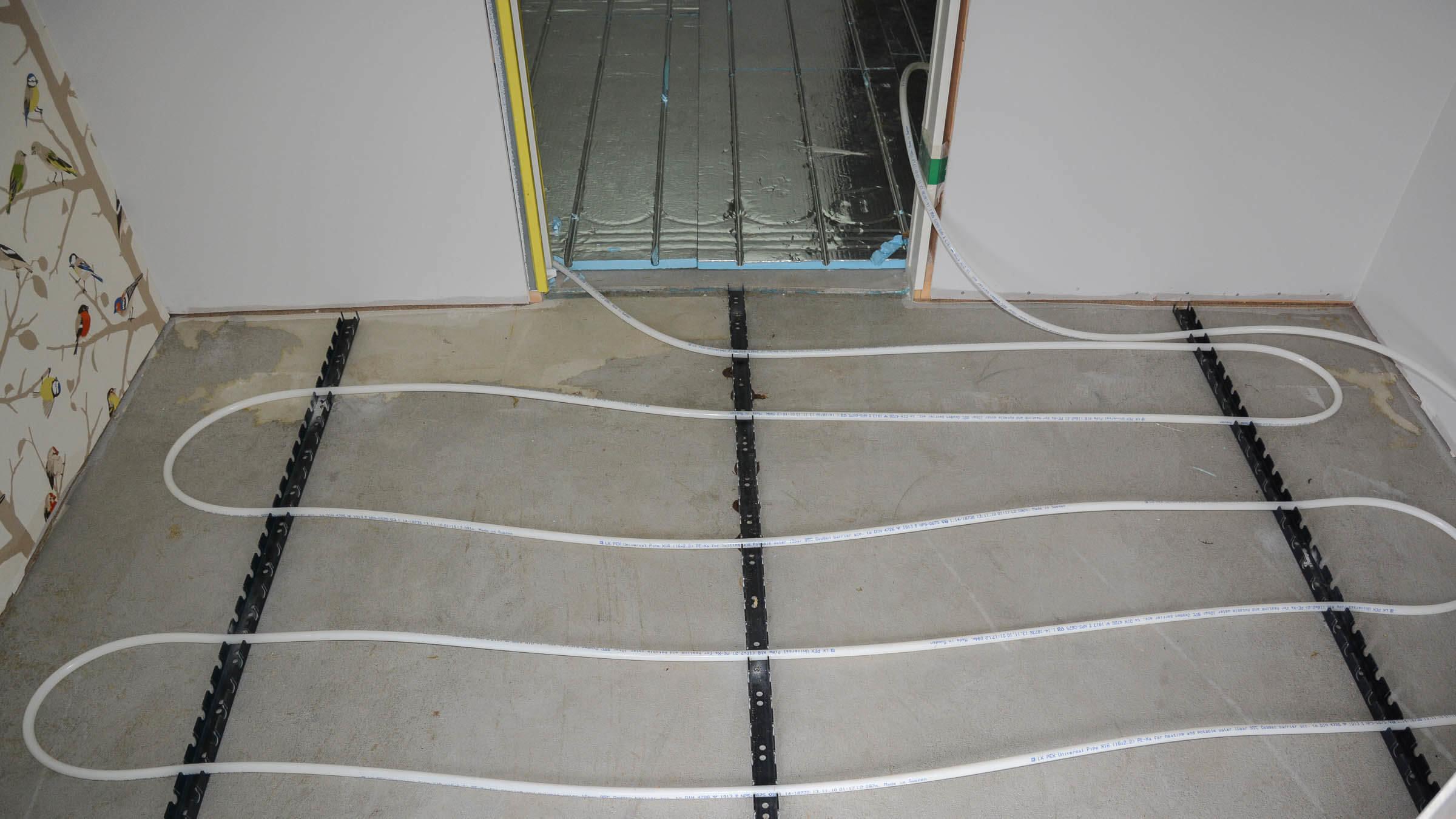 Sløyfer for gulvvarme legges på betonggulv i entre